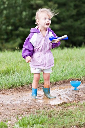 Cute little girl playing in the mud with ice cream scoops. Stock Photo - 5646887