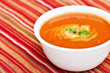 Tomato soup garnished with cream and basil leaves  photo
