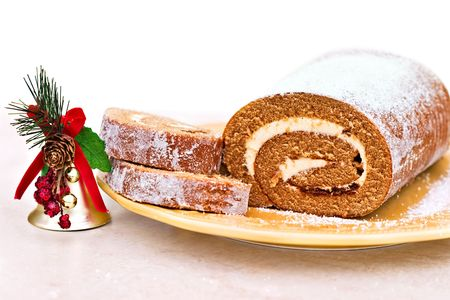 Delicious Pumpkin Roll, sliced so that the cream cheese filling is showing. White background with room for text. Stock Photo