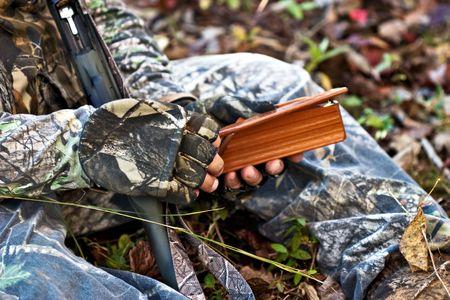 Close-up of a turkey hunter working a turkey box call. photo