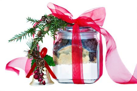 A Christmas gift of ingredients for Chocolate Chip Cookies in a jar decorated with pine bough and red ribbons. photo