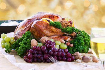 Roasted turkey on holiday table ready to eat. Selective focus on turkey. Stock Photo