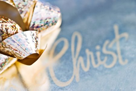 Shiny gold gift bow with beside the word Christ. Stock Photo