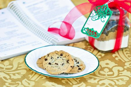 Chocolate Chips Cookies with a gift of cookie mix in a jar with blank card. Shallow DOF with cook book in the background.  photo