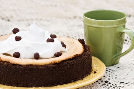 bakery products:  Cheesecake garnished with chocolate covered coffee bean with shallow DOF.