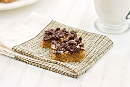 Peanut Butter Bars with Chocolate Chips on an old white table with fresh milk. Shallow DOF. photo