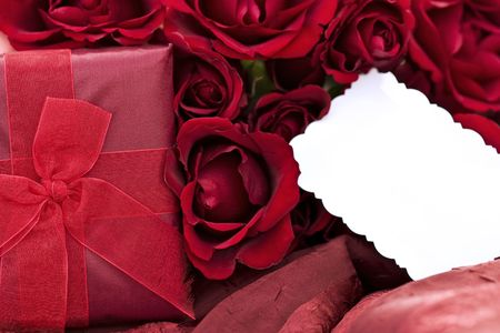 Beautiful gift box with a dozen red roses and blank card lying on a two toned red background. Extreme shallow DOF with focus on gift and center roses.  photo