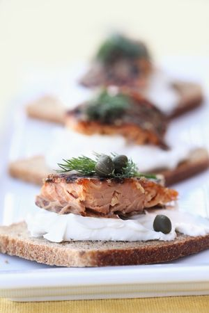 capers: Delicious seasoned smoked salmon with dill and capers served on rye.  Stock Photo
