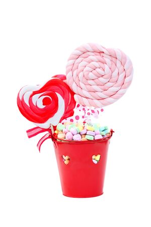 Fun heart shaped lollipops in a red container with heart shaped candies.  photo