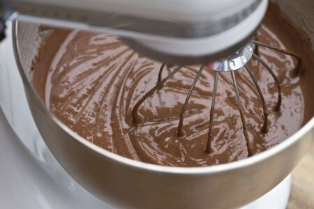 Chocolate cake batter being mixed in an electric mixer.