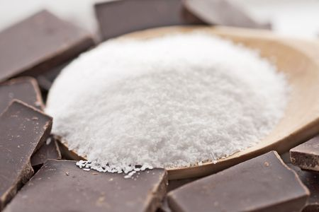 Wooden spoon filled with sea salt and surrounded by blocks of chocolate.  photo
