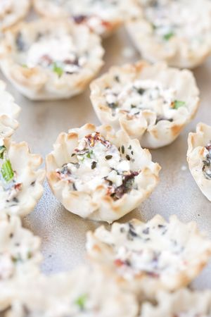 mini oven: Close up of mini goat cheese, basil and sun dried tomato tarts uncooked and ready for the oven. Shallow DOF with selective focus on center tart. Stock Photo