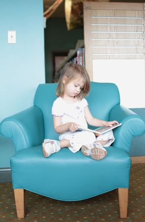 storytime: Little girl sitting in a colorful chair looks at or is reading a book.