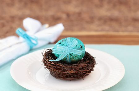 Blue speckled Easter egg in nest. Traditional blown egg filled with chocolate, but could also be used as a regular dyed egg. Shallow DOF. photo