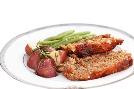 Meatloaf dinner with roasted red potatoes and green beans isolated on white. Extreme shallow DOF. photo
