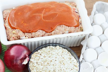 Freshly prepared meatloaf with catsup ready for the oven with ingredients. photo