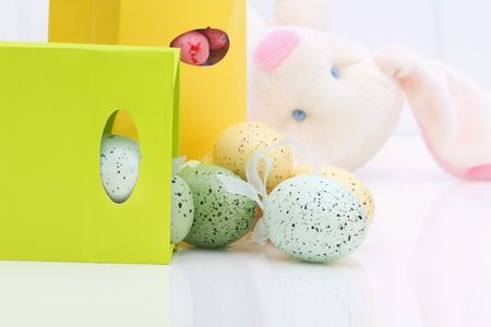 Beautiful Easter eggs spilling from a giftbag. Cute bunny in the background. Shallow DOF. Stock Photo - 6588572