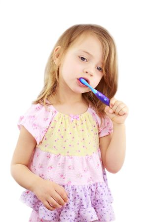 Cute little girl in pink pajamas is brushing her teeth against a white background.