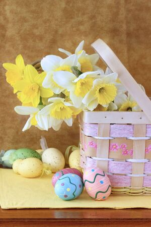 Easter eggs and daffodils in a pretty basket. Shallow DOF. photo