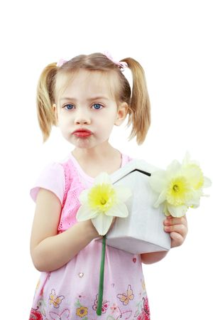 puckered lips: Adorable little girl blows a kiss for Mommy while holding fresh picked flowers and a giftbox.