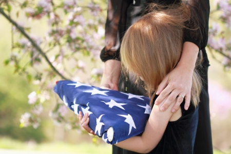 Daughter holding a parents folded American flag with a womans arms wrapped around her.