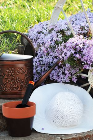 path cottage garden: A sunhat with flower pot, trowel and watering can sitting by a bed of garden phlox. Stock Photo