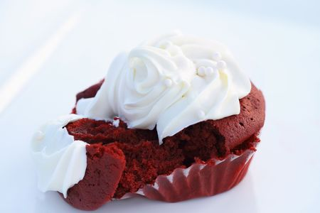Broken Red Velvet cupcake on a white dish. Shallow DOF. photo