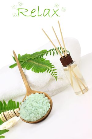 salts: Green bath salts in a wooden spoon with essential oils and white towel. Extreme shallow DOF with selective focus on bath salts. Room for your text. Stock Photo