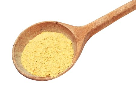 Nutritional yeast flakes in a wooden spoon isolated on white  Stock Photo