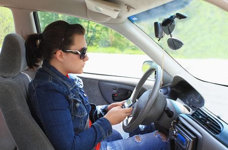 distracted: Teen drives car while distracted by text messaging on cell phone