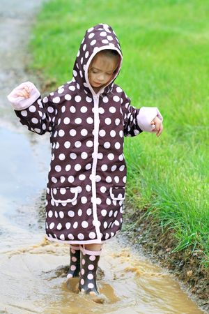 Little girl walking through a mud puddle in her rain coat and boots.