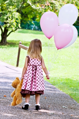 pink teddy bear: Little girl dragging her teddy bear and carrying a bunch of white and pink balloons.