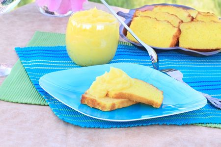 Lemon pound cake served with a creamy lemon curd on a colorful background.