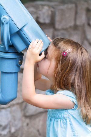 Little girl looks intently through binoculars at the world around her.