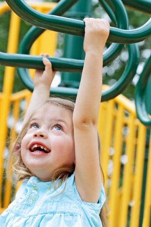 3 year old: Happy little girl crosses monkey bars at the playground. Extreme shallow DOF on forearm grabbing bar. Stock Photo