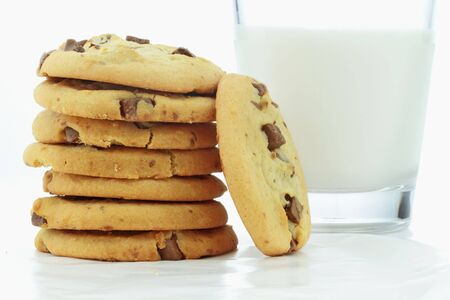 Chocolate chip cookies and a glass of milk on wax paper.