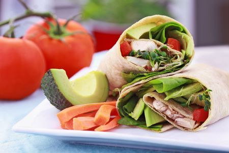 Vegan sandwich wrap with Lavish bread made from flax, oats and whole wheat. Stuffed with fresh spinach, sprouts, mushrooms, red peppers and avocados for a healthy lunch. Stock Photo