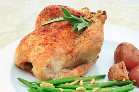 Roasted Cornish Hen with red potatoes and green beans sauteed with sliced almonds. Stock Photo