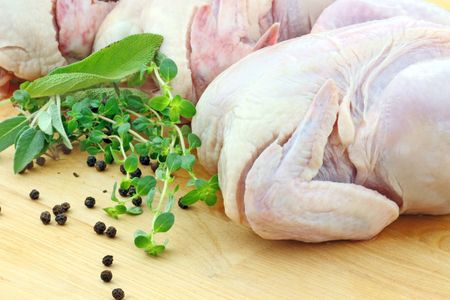 Fresh uncooked chicken with herbs on a cutting board. Shallow DOF.
