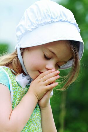 Little AmishMennonite child bows her head to pray. Stock Photo