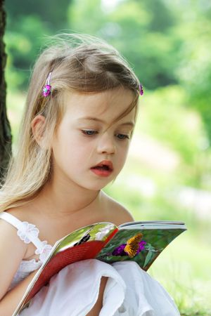 under a tree: Little girl sits outdoors under a tree reading a book about butterflies.