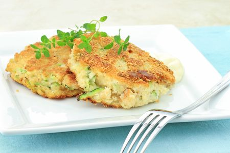 Healthy vegetarian Zucchini Crab Cakes served with horseradish sauce and a sprig of thyme.
