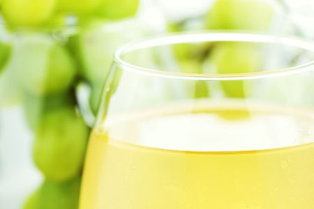 and grape juice: White grape juice in wine glasses with grapes in background. Water drops at 100%.