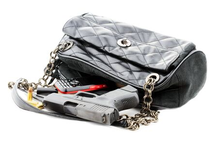 concealed: Carried concealed. Handgun and accessories falling from a womans purse. Isolated on white with light shadow.