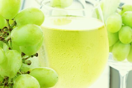 and grape juice: White grape juice in wine glasses with fresh grapes.