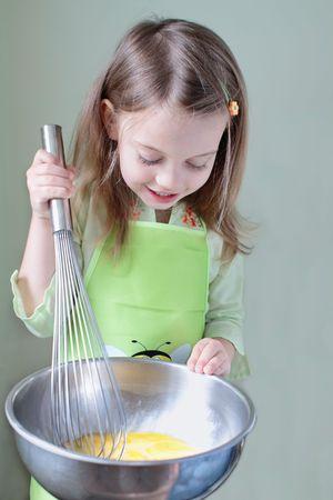 scrambling: Bambina utilizza un frullare extra large per battere le uova per la prima colazione. Alcuni sfocatura di movimento su frullare dove la bambina � battere le uova.