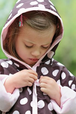 Little girl dresses herself in a raincoat. Stock Photo