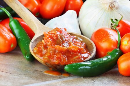 Rustic wooden spoon filled with spicy fresh salsa, surrounded by freshly picked and washed ingredients.