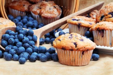 新鮮なブルーベリーの木のスプーンおよび枝編み細工品バスケットからこぼれるとおいしい自家製のブルーベリーのマフィン。 写真素材