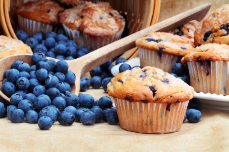 Delicious homemade blueberry muffins with fresh blueberries spilling from a wooden spoon and wicker basket. Stock Photo - 7387283